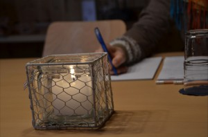 Kerze, im Hintergrund schreibende Hand